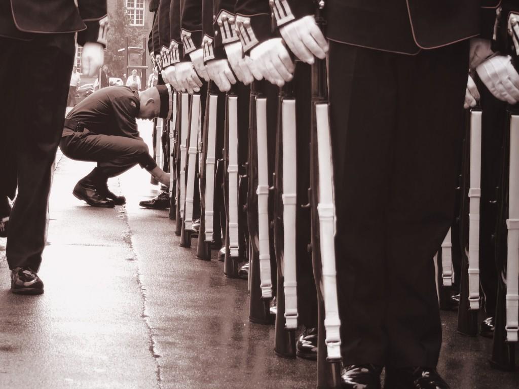 Uniformkledt ung mann sitter på huk og knytter sko.